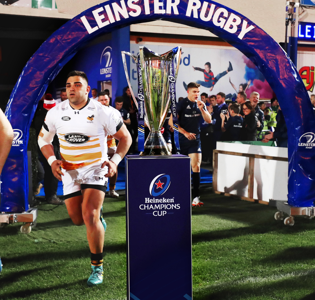 Leinster rugby players running past a trophy