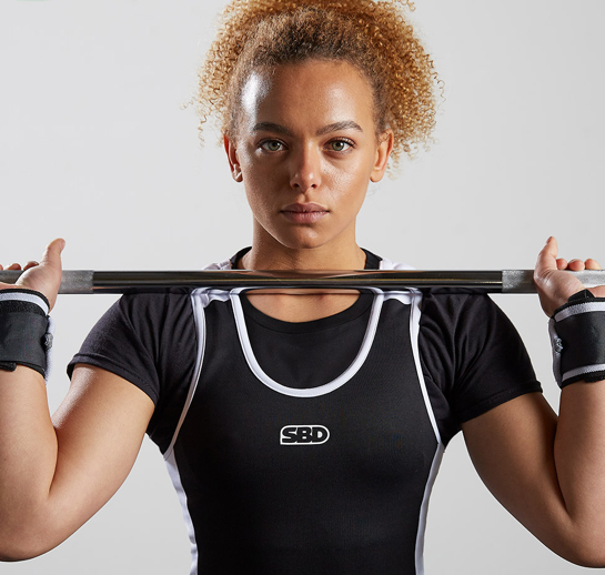 curly haired woman holds bar bell